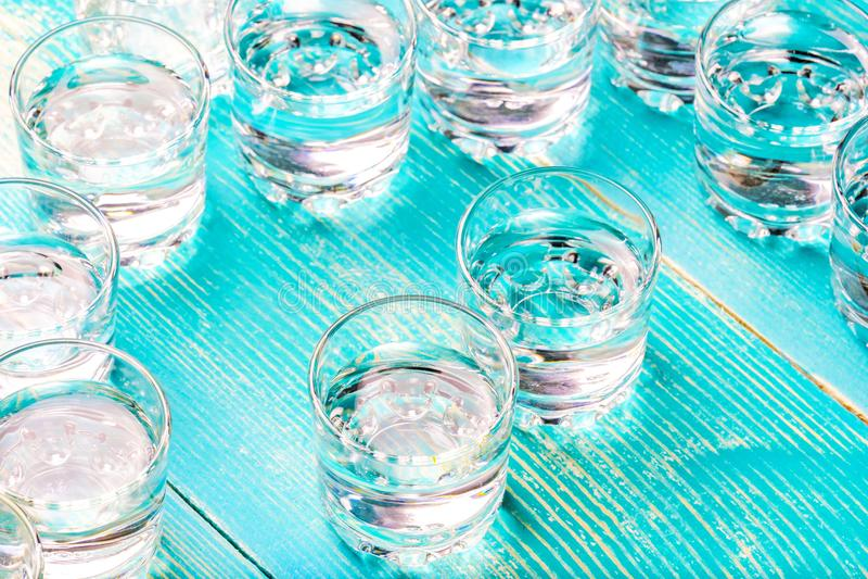 Χαοτικά τακτοποιημένα γυαλιά γυαλιού από κάτω από ένα ποτό σε έναν μπλε πίνακα στοκ εικόνα