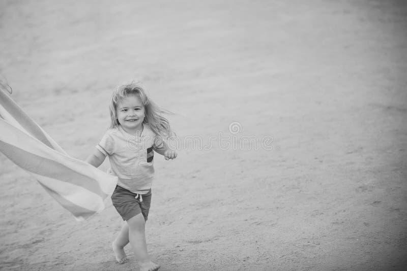 Χαρά το παιδί εν πλω Μικρό αγόρι παιδιών με το ευτυχές πρόσωπο χαμόγελου που τρέχει κατά μήκος της παραλίας στοκ φωτογραφίες