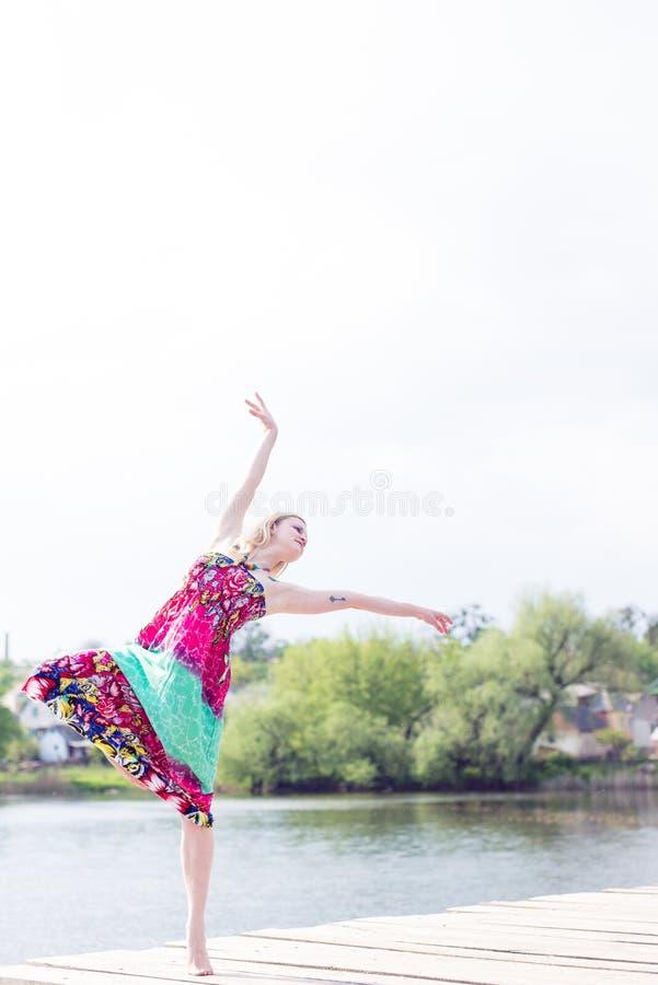 Χαρά χορού: όμορφη ξανθή νέα λεπτή γυναίκα που απολαμβάνει το τέντωμα στο μακρύ ελαφρύ φόρεμα στη λίμνη νερού στο καλοκαίρι πράσι στοκ φωτογραφία