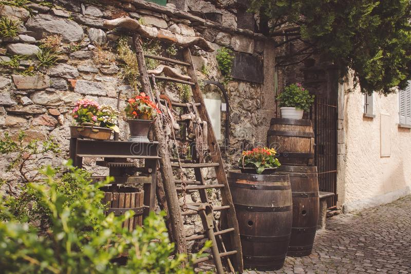 Χαρακτηριστικά εργαλεία και λουλούδια Ticinese που κλίνουν σε έναν τοίχο πετρών στοκ εικόνα