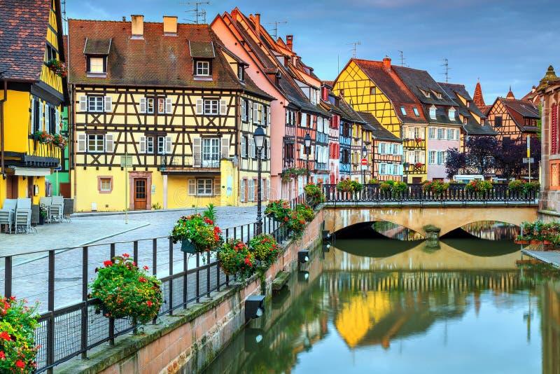 Χαρακτηριστικές μεσαιωνικές μισό-εφοδιασμένες με ξύλα προσόψεις που απεικονίζουν στο νερό, Colmar, Γαλλία στοκ φωτογραφίες