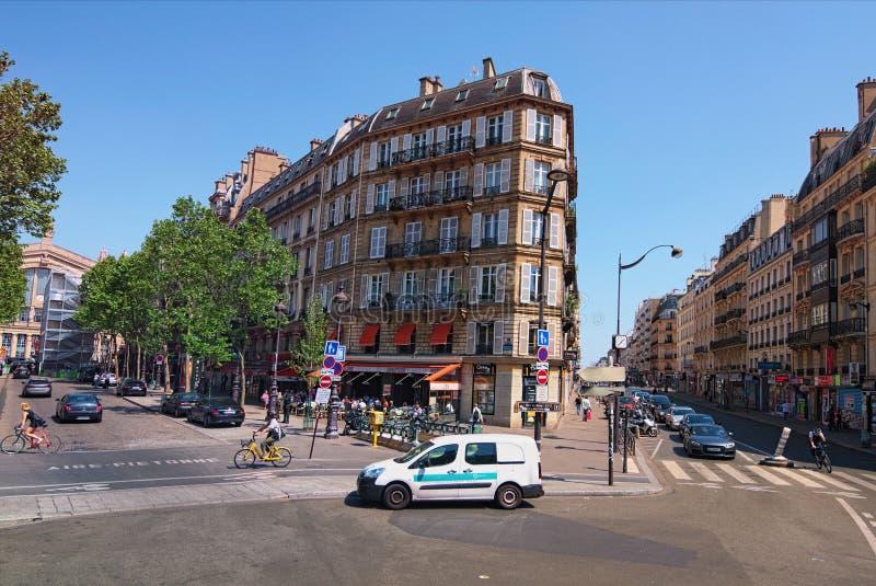 Χαρακτηριστική γωνία του παλαιού τριγωνικού κτηρίου Αυτοκίνητα, ποδηλάτες και άνθρωποι στην οδό της πόλης ημέρα ηλιόλουστη στοκ εικόνες