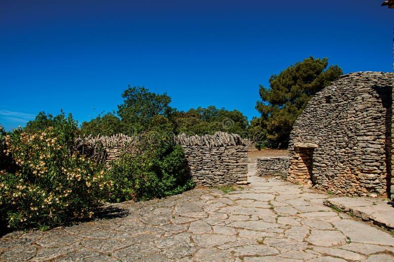 Χαρακτηριστική καλύβα φιαγμένη από πέτρα με τον ηλιόλουστο μπλε ουρανό, στο χωριό Bories, κοντά σε Gordes στοκ φωτογραφία
