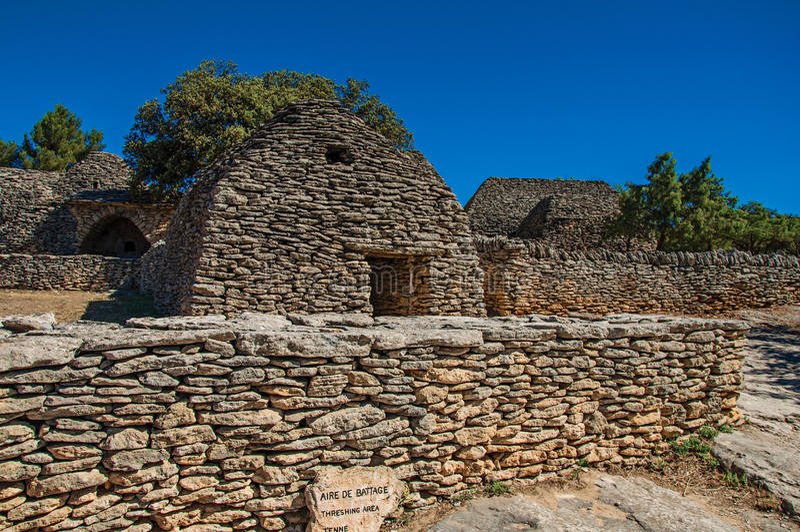 Χαρακτηριστική καλύβα φιαγμένη από πέτρα με τον περιτοιχισμένο φράκτη και ηλιόλουστο μπλε ουρανό, στο χωριό Bories, κοντά σε Gord στοκ εικόνες