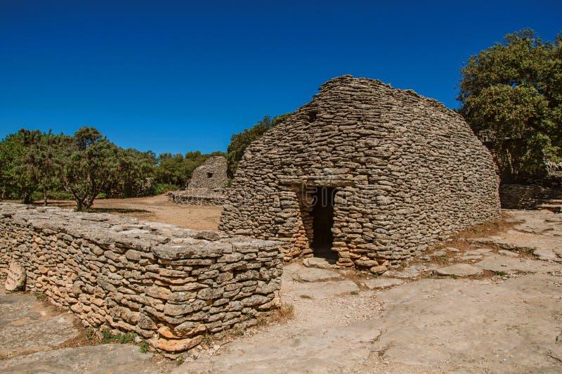 Χαρακτηριστική καλύβα φιαγμένη από πέτρα με τον περιτοιχισμένο φράκτη και ηλιόλουστο μπλε ουρανό, στο χωριό Bories, κοντά σε Gord στοκ φωτογραφία με δικαίωμα ελεύθερης χρήσης