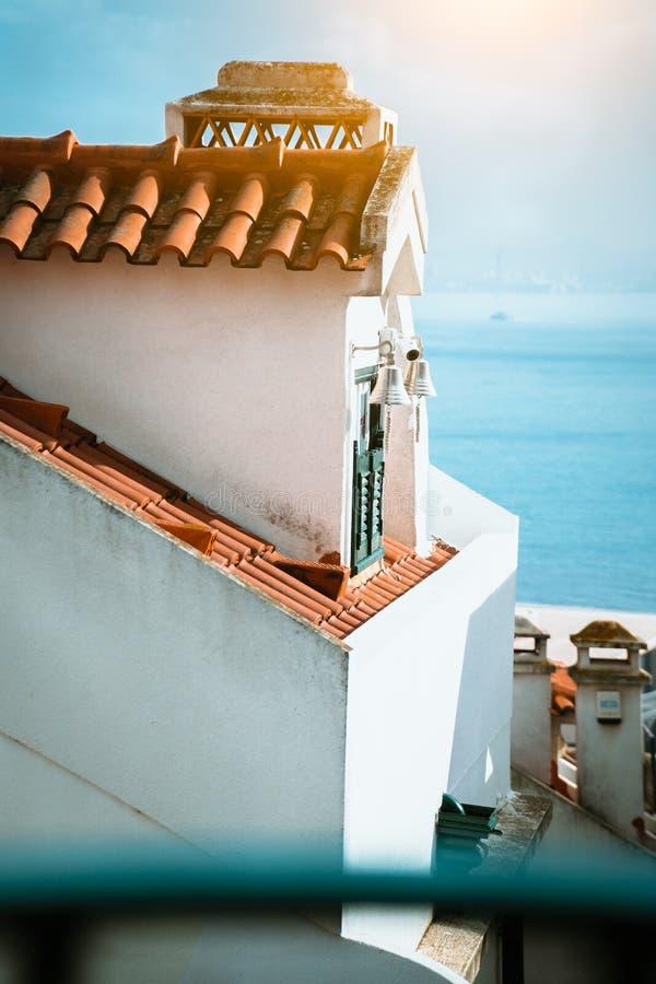 Χαρακτηριστική στέγη της Λισσαβώνας με τα κόκκινα κεραμίδια και ένα παράθυρο με τα παραδοσιακά ζωηρόχρωμα παραθυρόφυλλα Οδοί και  στοκ φωτογραφία με δικαίωμα ελεύθερης χρήσης