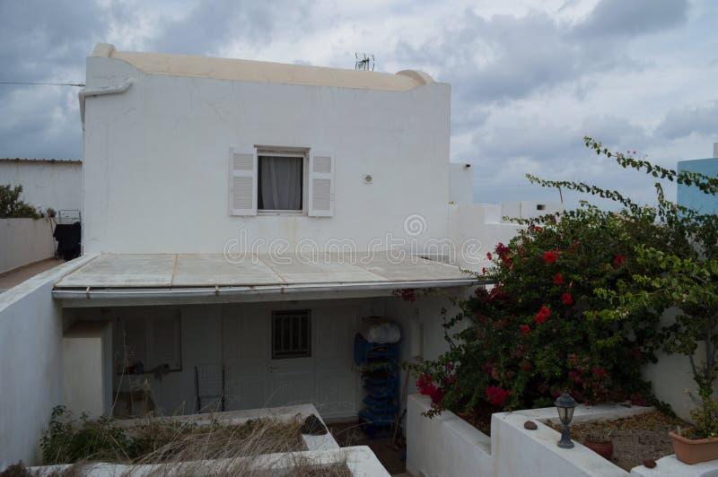 Χαρακτηριστικό ασπρισμένο Santorini σπίτι με την άποψη θάλασσας από κτυπημένο στοκ εικόνες