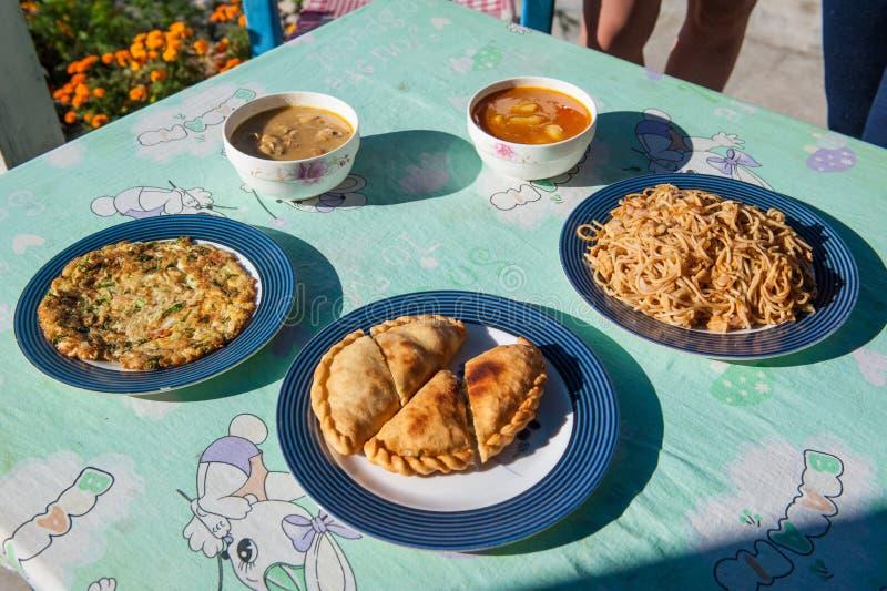 Χαρακτηριστικό νεπαλικό γεύμα στο κύκλωμα Manaslu, Ιμαλάια, Νεπάλ Ανάμεικτα ινδικά νεπαλικά τρόφιμα στον πίνακα Πιάτα και ορεκτικ στοκ φωτογραφία