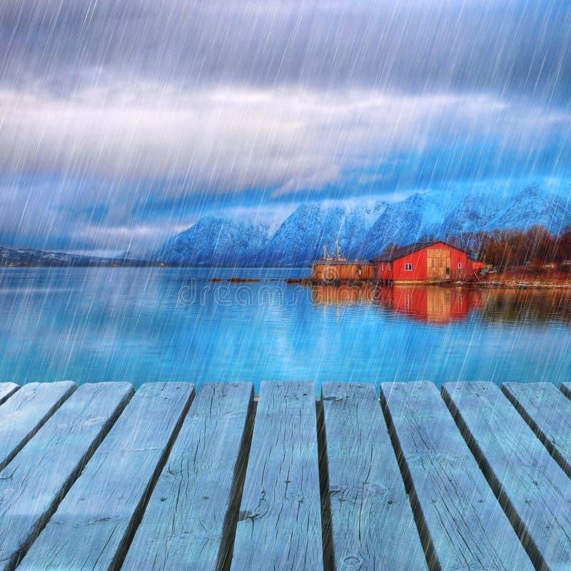 Χαρακτηριστικό Σκανδιναβικό κόκκινο σπίτι στη θάλασσα στο φιορδ με την αποβάθρα πλατφορμών στη βροχερή ημέρα στοκ φωτογραφία
