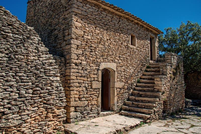 Χαρακτηριστικό σπίτι φιαγμένο από πέτρα με τη σκάλα και ηλιόλουστο μπλε ουρανό, στο χωριό Bories, κοντά σε Gordes στοκ εικόνες