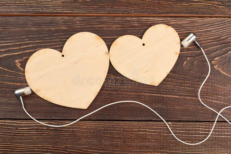 Χαρασμένα καρδιές και ακουστικά στο ξύλινο υπόβαθρο στοκ εικόνες με δικαίωμα ελεύθερης χρήσης
