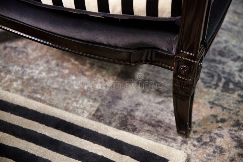 Χαρασμένα πόδια της λουστραρισμένης με λάκκα ξύλινης καρέκλας στοκ φωτογραφία