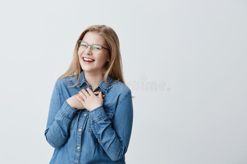 Χαρισματική και γοητευτική νέα Ευρωπαία γυναίκα με την ευθεία ξανθή τρίχα που φορά τα μοντέρνα γυαλιά και το πουκάμισο τζιν στοκ φωτογραφία
