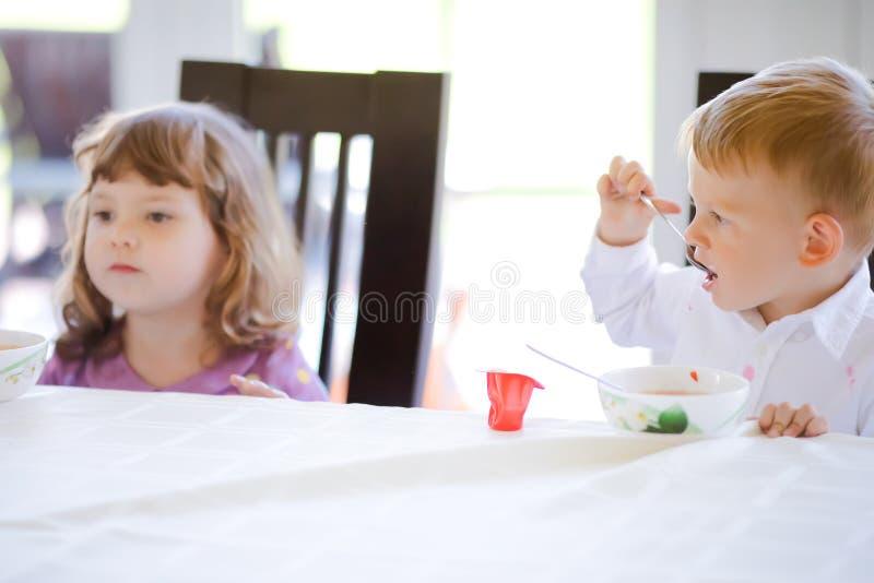 Χαριτωμένα αγόρι και κορίτσι μικρών παιδιών που τρώνε τη σούπα μαζί στ στοκ εικόνα με δικαίωμα ελεύθερης χρήσης
