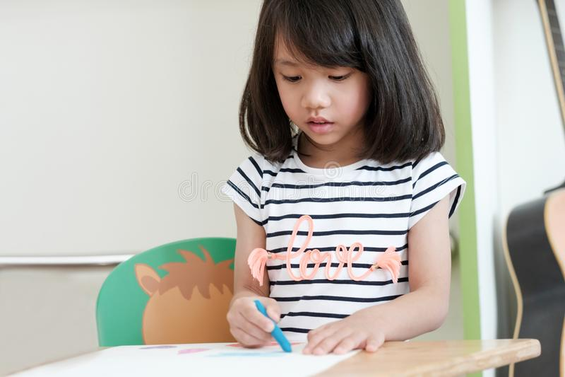 Χαριτωμένα ασιατικά μολύβια χρώματος σχεδίων κοριτσιών στην τάξη παιδικών σταθμών, στοκ φωτογραφίες