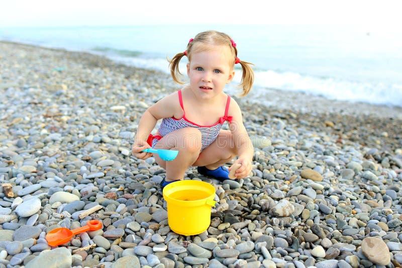 Χαριτωμένα ευτυχή παιχνίδια μικρών κοριτσιών στην παραλία στοκ εικόνα