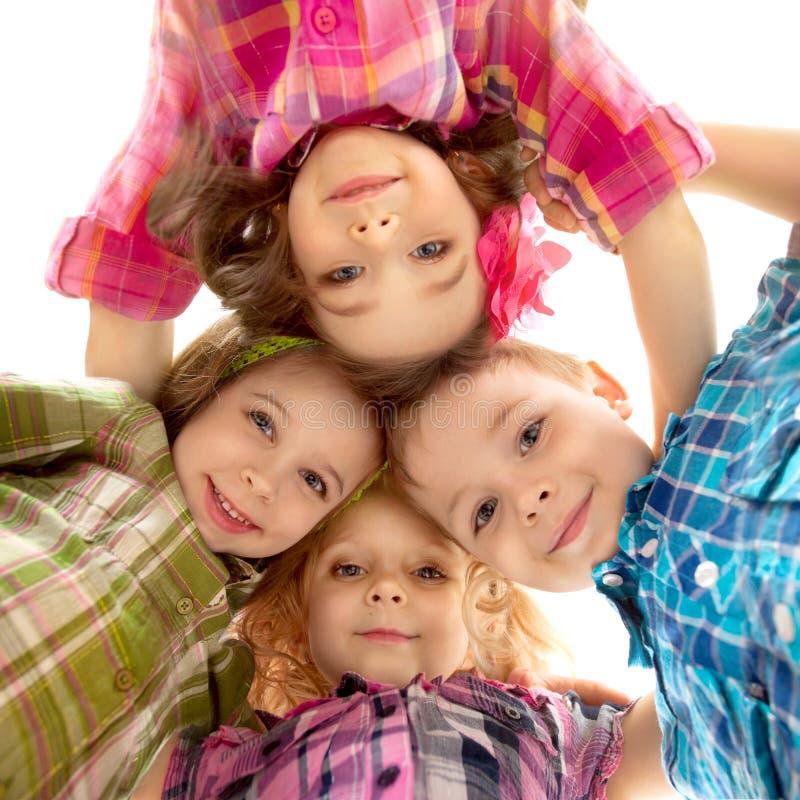 Χαριτωμένα ευτυχή παιδιά που φαίνονται κάτω και που κρατούν τα χέρια στοκ εικόνες