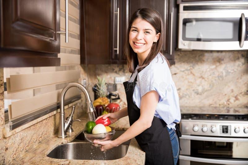 Χαριτωμένα λαχανικά πλύσης γυναικών για το μαγείρεμα στοκ φωτογραφία