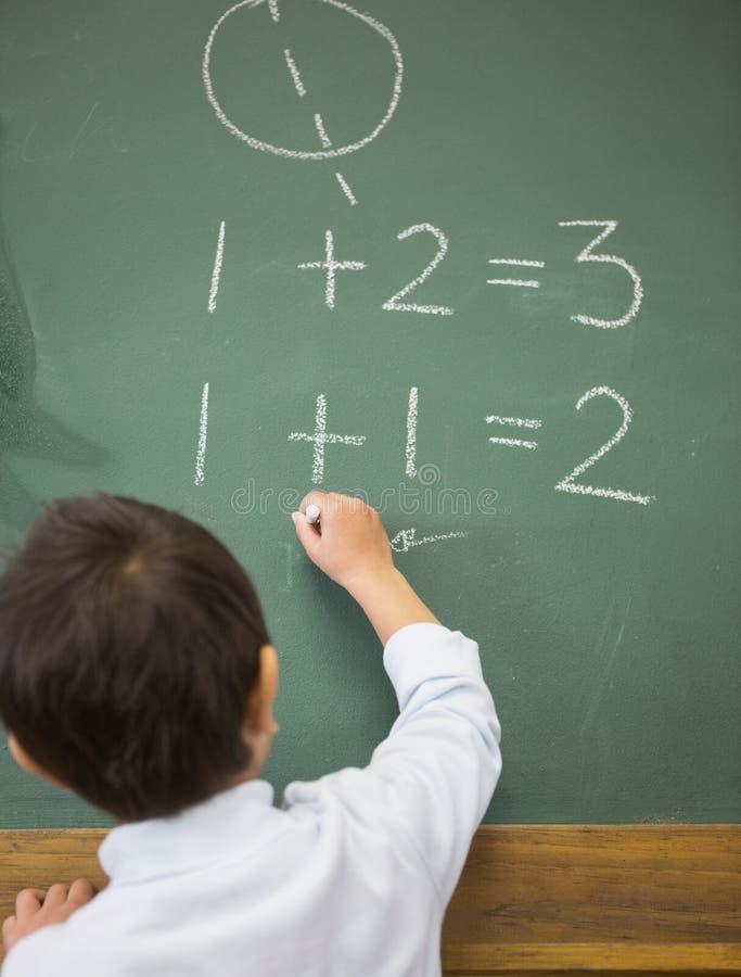 Χαριτωμένα μαθηματικά γραψίματος μαθητών στον πίνακα κιμωλίας στοκ εικόνες
