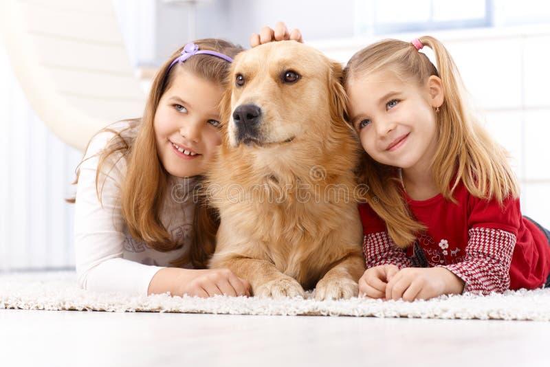 Χαριτωμένα μικρά κορίτσια με το χαμόγελο σκυλιών κατοικίδιων ζώων στοκ εικόνες με δικαίωμα ελεύθερης χρήσης