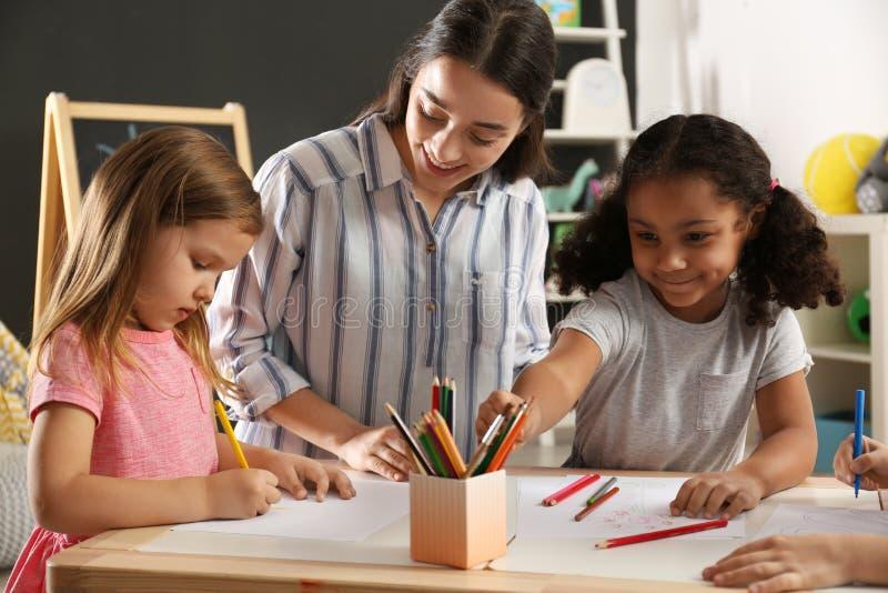 Χαριτωμένα μικρά παιδιά με το σχέδιο δασκάλων βρεφικών σταθμών στον πίνακα στον παιδικό σταθμό στοκ εικόνες