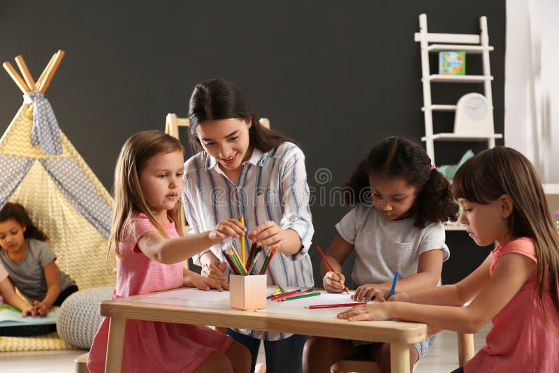 Χαριτωμένα μικρά παιδιά με το σχέδιο δασκάλων βρεφικών σταθμών στον πίνακα στον παιδικό σταθμό στοκ φωτογραφίες με δικαίωμα ελεύθερης χρήσης