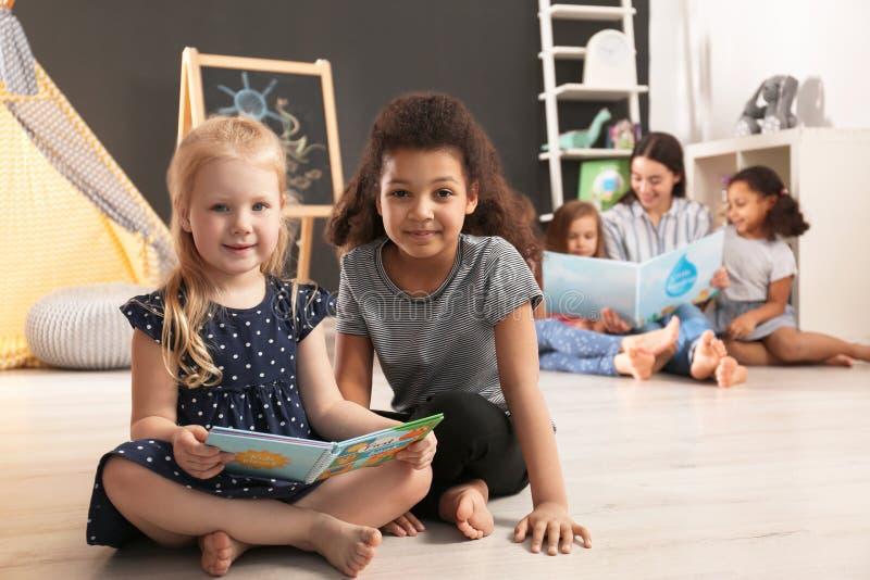 Χαριτωμένα μικρά παιδιά που διαβάζουν το βιβλίο στο πάτωμα στον παιδικό σταθμό Εσωτερική δραστηριότητα στοκ εικόνες με δικαίωμα ελεύθερης χρήσης