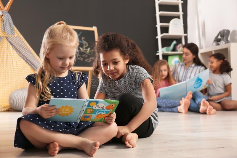 Χαριτωμένα μικρά παιδιά που διαβάζουν το βιβλίο στο πάτωμα στον παιδικό σταθμό Εσωτερική δραστηριότητα στοκ φωτογραφίες με δικαίωμα ελεύθερης χρήσης