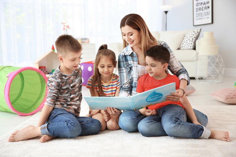 Χαριτωμένα μικρά παιδιά που διαβάζουν το βιβλίο στο πάτωμα στοκ εικόνες