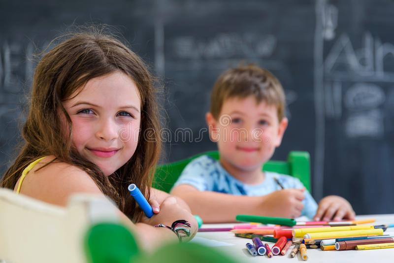 Χαριτωμένα μικρό κορίτσι και αγόρι που σύρουν και που χρωματίζουν με τις ζωηρόχρωμες μάνδρες δεικτών στον παιδικό σταθμό Δημιουργ στοκ εικόνα με δικαίωμα ελεύθερης χρήσης