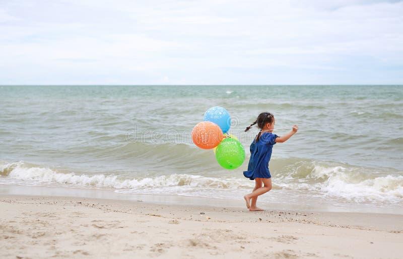 Χαριτωμένα μπαλόνια λίγου παιδιών παιχνιδιού κοριτσιών στην παραλία στοκ εικόνες