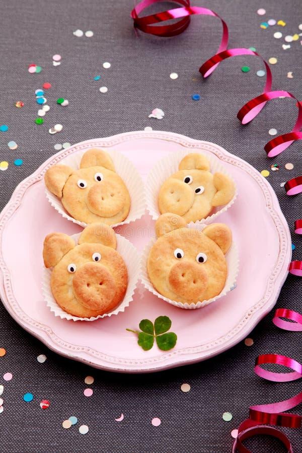 Χαριτωμένα μπισκότα που διαμορφώνουν τους μικρούς χοίρους στο ρόδινο πιάτο στοκ εικόνες