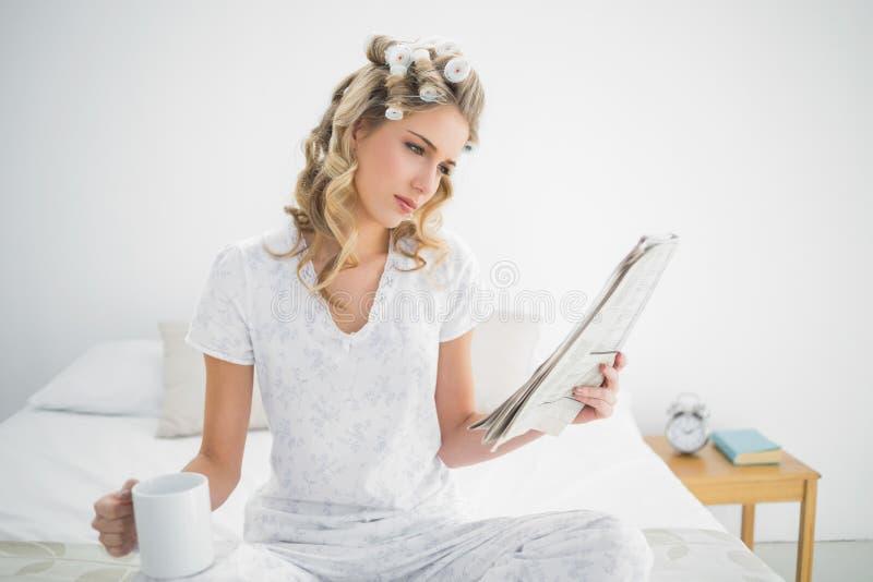 Χαριτωμένα ξανθά φορώντας ρόλερ τρίχας που διαβάζουν την εφημερίδα στοκ εικόνα