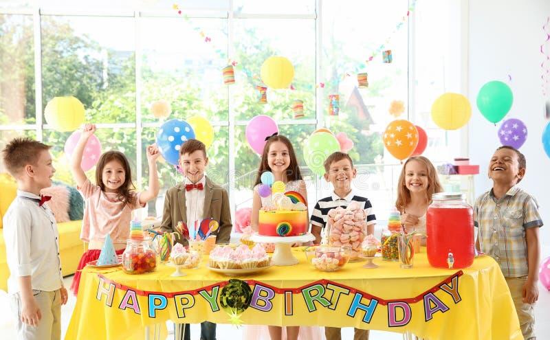 Χαριτωμένα παιδιά κοντά στον πίνακα με τις απολαύσεις στη γιορτή γενεθλίων στο εσωτερικό στοκ εικόνα