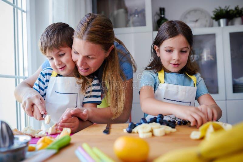 Χαριτωμένα παιδιά με τη μητέρα που προετοιμάζει ένα υγιές πρόχειρο φαγητό φρούτων στην κουζίνα στοκ εικόνα