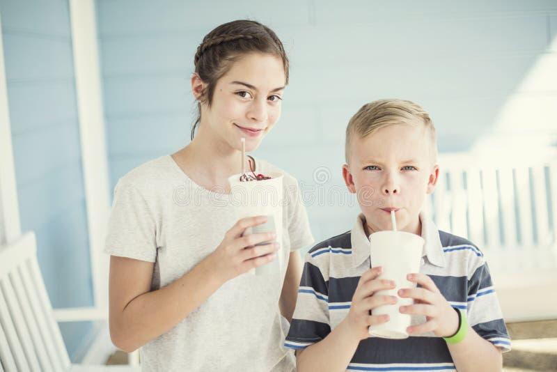 Χαριτωμένα παιδιά που πίνουν milkshakes ή αρωματικά ποτά από κοινού στοκ φωτογραφία
