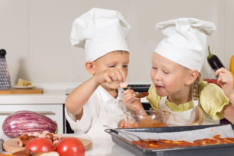 Χαριτωμένα παιδάκια που δοκιμάζουν τη σάλτσα για την πίτσα στοκ φωτογραφίες με δικαίωμα ελεύθερης χρήσης
