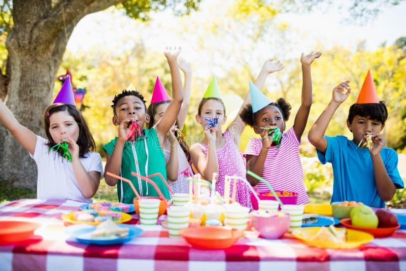 Χαριτωμένα παιδιά που έχουν τη διασκέδαση κατά τη διάρκεια μιας γιορτής γενεθλίων στοκ εικόνα