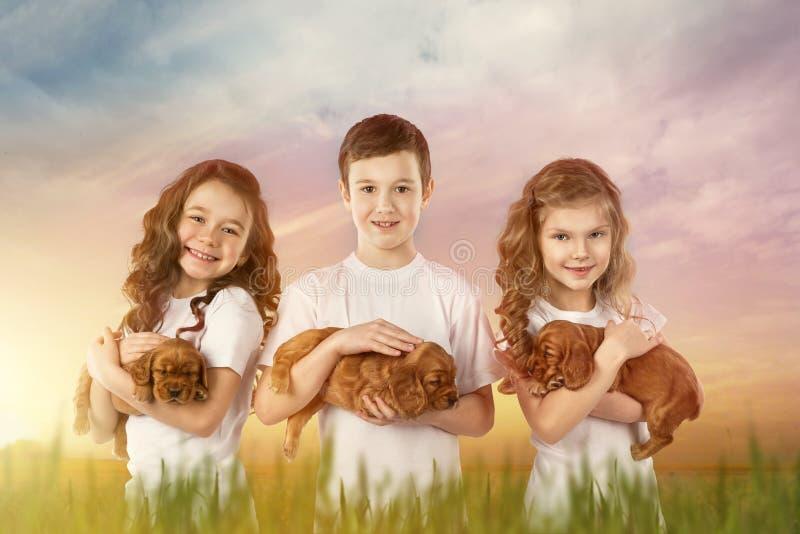 Χαριτωμένα παιδιά που κρατούν τα κόκκινα κουτάβια υπαίθρια Φιλία κατοικίδιων ζώων παιδιών στοκ φωτογραφίες με δικαίωμα ελεύθερης χρήσης