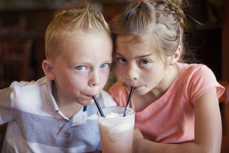 Χαριτωμένα παιδιά που μοιράζονται ένα ιταλικό ποτό σόδας μεντών σε έναν καφέ στοκ φωτογραφία