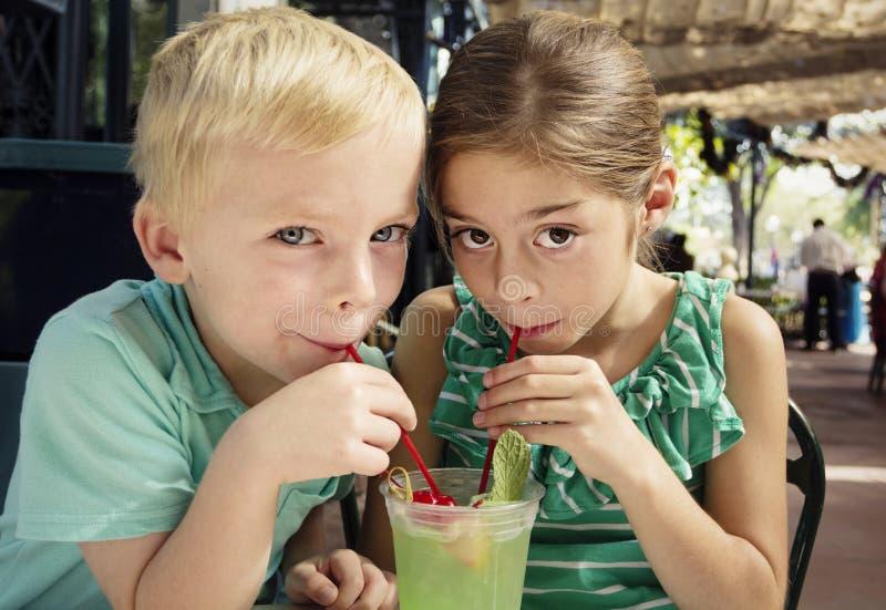 Χαριτωμένα παιδιά που μοιράζονται ένα ποτό σαλέπι μεντών σε έναν καφέ στοκ εικόνες