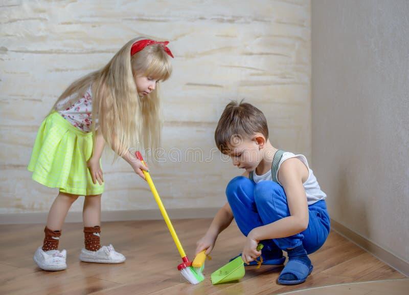 Χαριτωμένα παιδιά που χρησιμοποιούν τη σκούπα και dustpan παιχνιδιών στοκ φωτογραφία με δικαίωμα ελεύθερης χρήσης