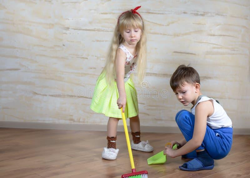 Χαριτωμένα παιδιά που χρησιμοποιούν τη σκούπα και dustpan παιχνιδιών στοκ εικόνα