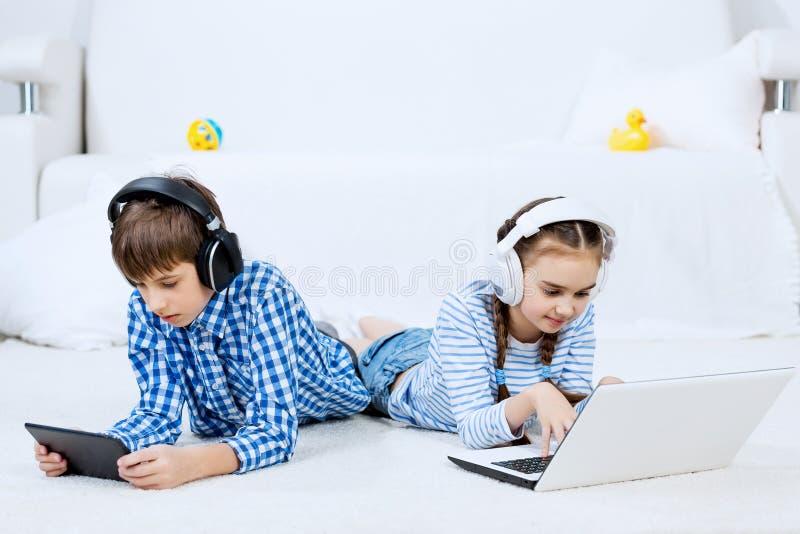 Χαριτωμένα παιδιά που χρησιμοποιούν τις συσκευές στοκ φωτογραφίες με δικαίωμα ελεύθερης χρήσης