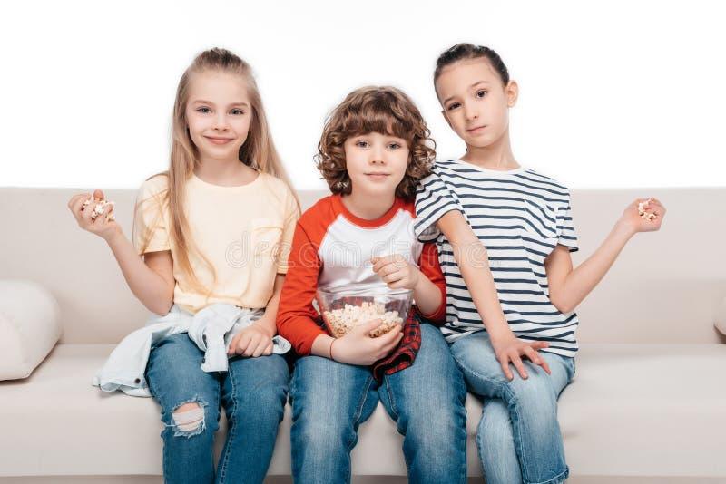 Χαριτωμένα παιδιά στον καναπέ με popcorn στοκ εικόνες