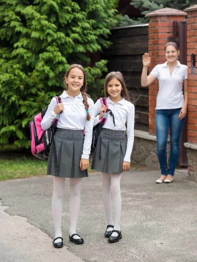 Χαριτωμένα χαμογελώντας κορίτσια που αφήνουν το σπίτι για το σχολείο στο πρωί στοκ φωτογραφία