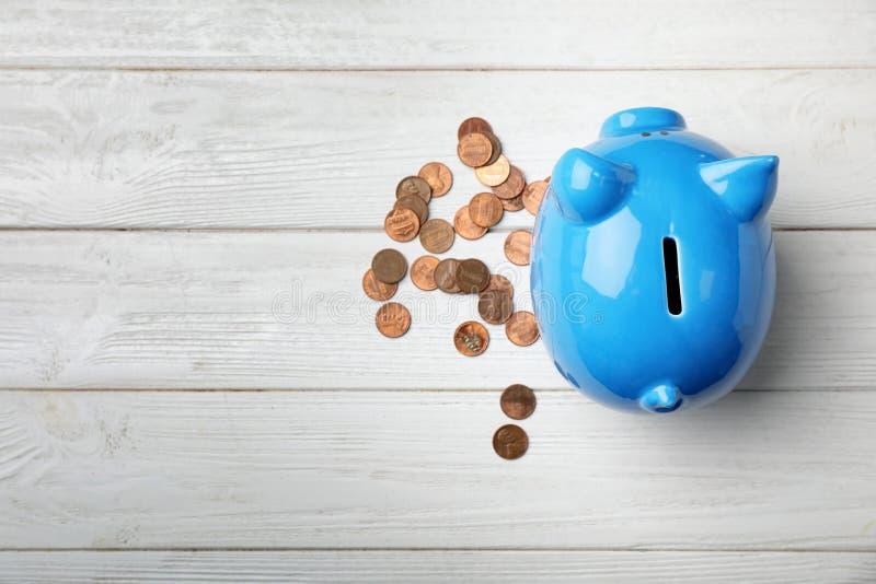 Χαριτωμένα piggy τράπεζα και νομίσματα στο ξύλινο υπόβαθρο στοκ φωτογραφία με δικαίωμα ελεύθερης χρήσης