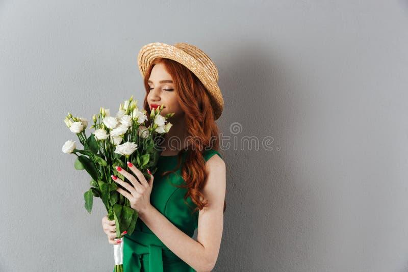 Χαριτωμένα redhead νέα λουλούδια εκμετάλλευσης γυναικών στοκ εικόνα