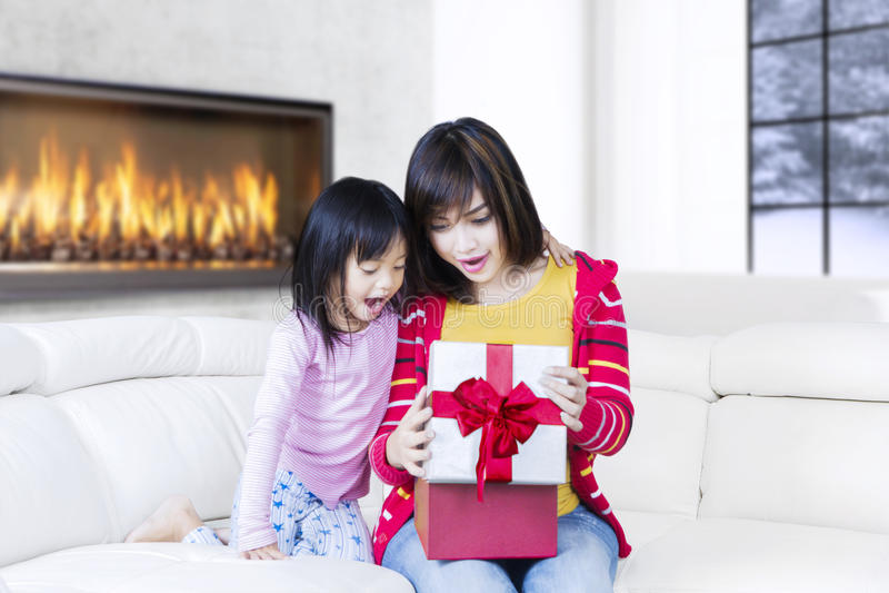 Χαριτωμένες κορίτσι και μητέρα που εκπλήσσονται με το δώρο στοκ φωτογραφία