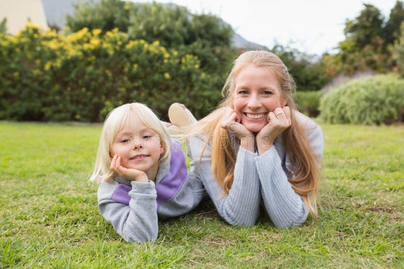 Χαριτωμένες κόρη και μητέρα που χαμογελούν στη κάμερα στοκ φωτογραφίες
